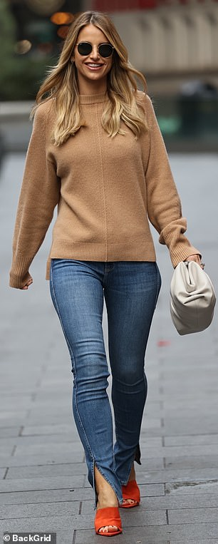 She emphasised her long legs in her tight jeans and added a bold pop of colour with her bright orange heels