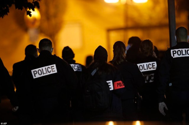 French police gather outside a middle school in a Parisian suburb of Friday night after a history teacher was decapitated