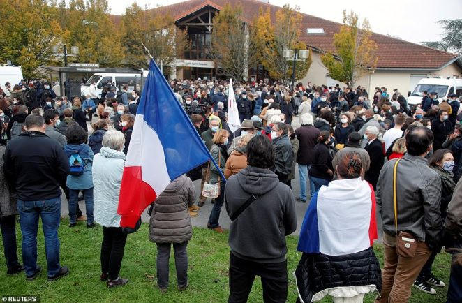 People gather in front of the Bois d'Aulne college after the attack in the Paris suburb of Conflans St Honorine
