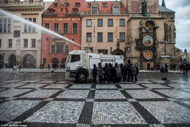 Riot police use water cannon against protestors at the Old Town Square as hundreds of demonstrators, including football supporters, protest against the Czech government's new measures to slow the spread of the Covid-19 coronavirus in Prague on October 18