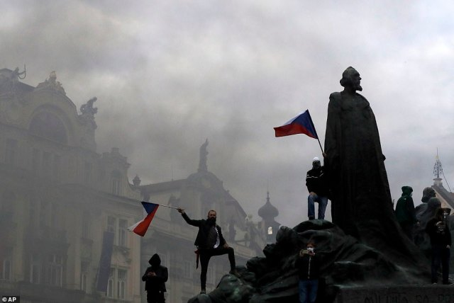 Protesters wave flags at the Old Town Square. Czech police used tear gas and a water cannon to disperse crowd of hundreds of violent protesters who attacked them after a rally in Prague against the government's restrictive measures imposed to slow the spread of the coronavirus infections