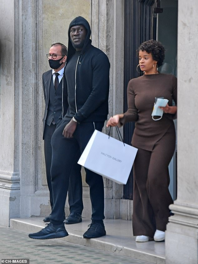 Success: His assistant also carried a white bag with the name of the gallery written on the front