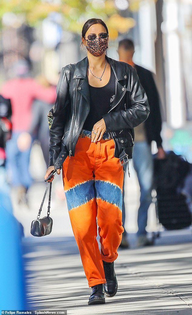 Chic: The Russian beauty was unmissable, as she rocked her bright orange trousers, which featured denim patches across her upper-thighs and at the waist