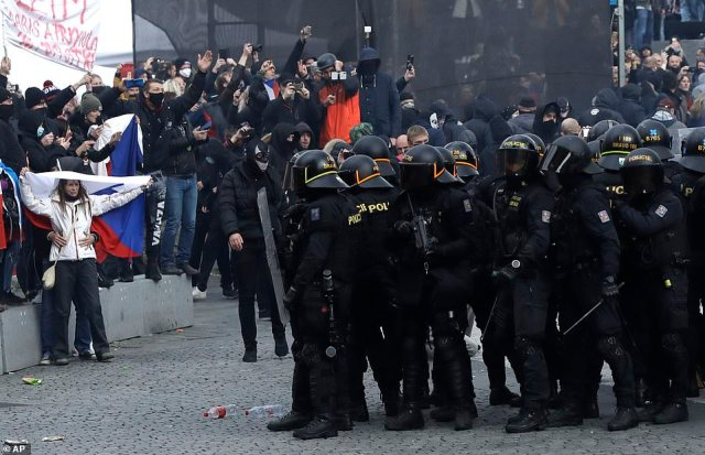 Police clash with protesters at the Old Town Square in Prague, Czech Republic. Officials have warned that hospital admissions are set to rise sharply until the restrictions show an impact