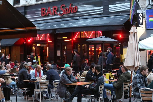 Crowds of revellers wrap up warm as they sit at tables placed outside bars and restaurants in central London's Soho
