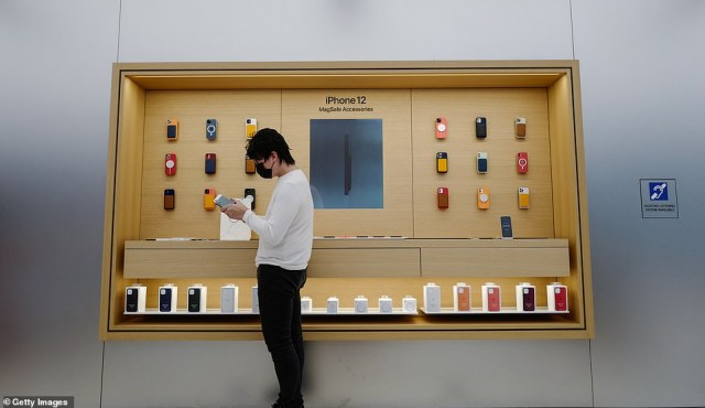 Jun, the first customer in Sydney's Apple Store, enjoys the feel of the new iPhone 12, which is notable for its flat edges unlike the curved edges of recent iPhone models