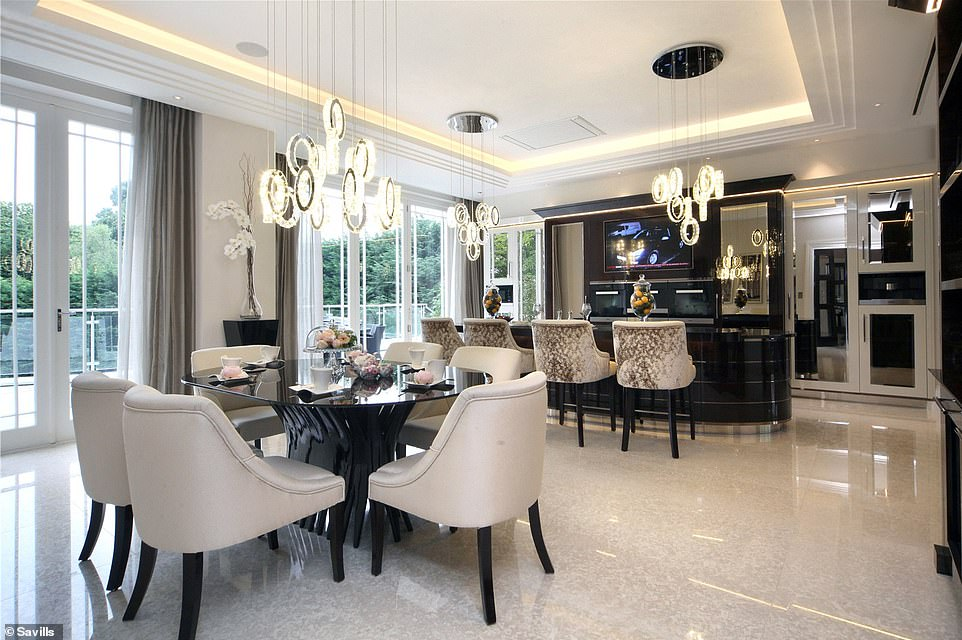 The luxury feel of this kitchen is created with some statement lighting and striking furniture