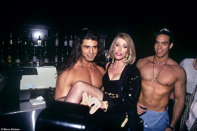 """Birthday girl: Joan Rivers is seen at Club USA, in 1993 where she celebrated her birthday while being hoisted in the air by shirtless men. The author writes, 'These guys, like totally buffed out models, were like carrying her around and I'm snapping pictures and they did a birthday cake and at some point, she pulled me aside and she said """"Would you please not use those pictures of the guys."""" Her stand-up comedy was so raunchy yet she was shy about this photo'"""