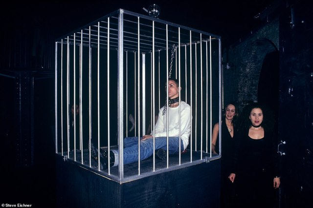 Caged in: An art installation is seen at the Tunnel in 1993. 'I never knew what to expect when I walked into a club on any given night,' Eichner says. 'The creativity and push to excite and entertain was a key theme running through 1990s clubland. Art installations were a big part of keeping things fresh and exciting. On this night an 'insane asylum' theme was the expression du jour. Nurses and doctors roamed around performance artists in cages,there was a person in a straight jacket and another in a padded cell. The inmates were running the asylum'