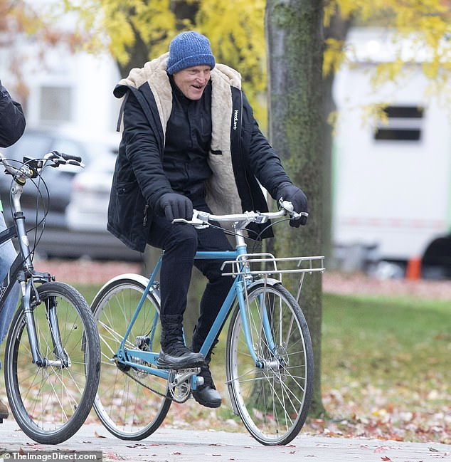 Bike tour: His co-star Harrelson, 59, was spotted on the set with a light blue bike but also stayed bundled up
