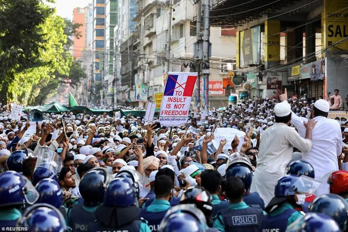 BANGLADESH: A banner with a cross through a French flag and a slogan saying 'to insult is not freedom' is held up during a march watched by police in Dhaka today