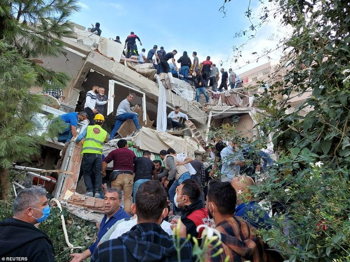 Locals and officials search for survivors at a collapsed building after a strong earthquake struck the Aegean Sea on Friday and was felt in both Greece and Turkey