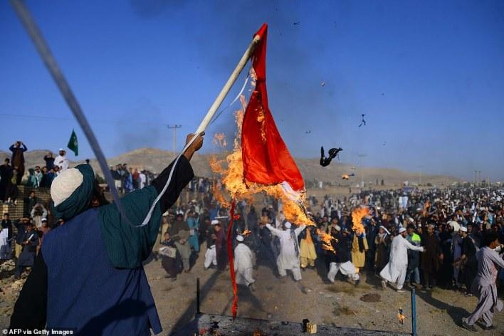 Muslim demonstrators burn a French flag during a protest against Emmanuel Macron inGuzargah, Afghanistan