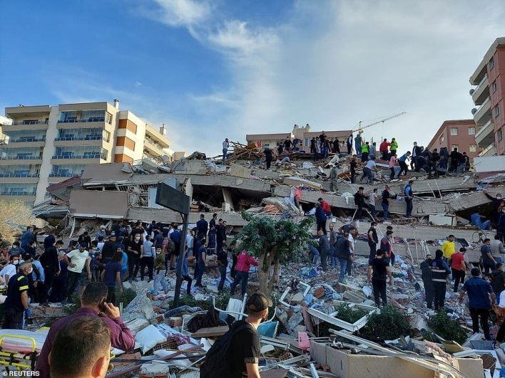 A huge crowd of locals and emergency officials search the debris of one of the collapsed buildings in Izmir today