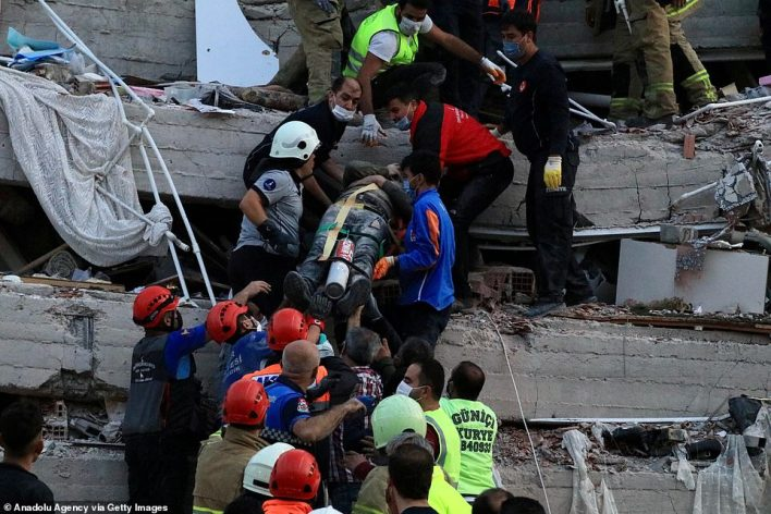 Wounded people are cut free from the wreckage of a toppled building in Izmir, Turkey, after the quake struck