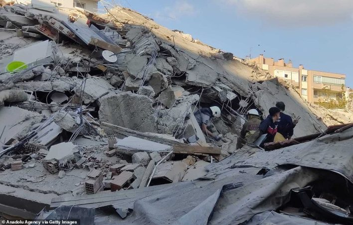 Emergency responders wearing white helmets scour the rubble today after this building was toppled by the earthquake