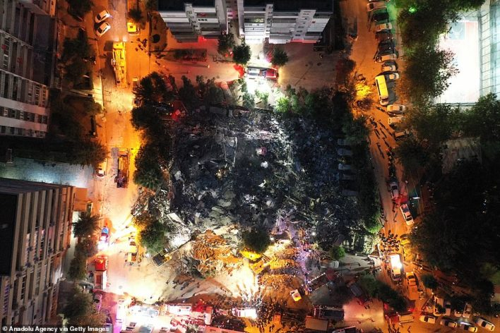 The rubble of a flattened building is seen from the air as night falls over Izmir, Turkey, after the city was hit by an earthquake