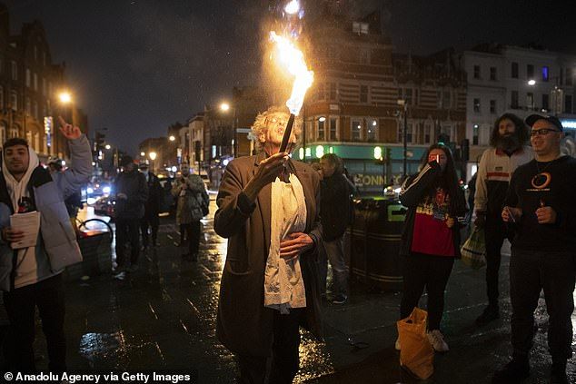 Piers Corbyn, 73, lead a 'street-party' protest against Covid lockdown rules in north London last night and performed a fire breathing party trick for the crowd