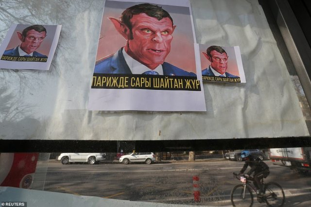 """Placards reading """"The yellow Devil is in Paris"""" hang in a window as a mark of a protest against the publications of a cartoon of Prophet Mohammad in France and French President Emmanuel Macron's comments, in Almaty, Kazakhstan today"""