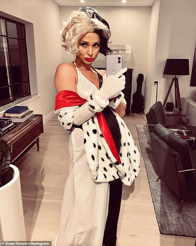 Scary: Pregnant former Bachelor winner Anna Heinrich dressed up as Disney villain Cruella Deville in a black and white frock with a matching wig and a Dalmatian print shoal