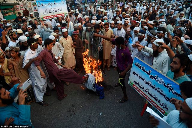 Protesters burn effigy of French President Emmanuel Macron during an anti-French protest in Karachi today