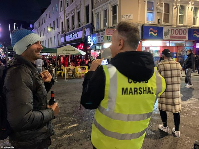 A reveller holding a beer bottle is seen talking to a Covid marshall in Soho ahead of England's new shutdown