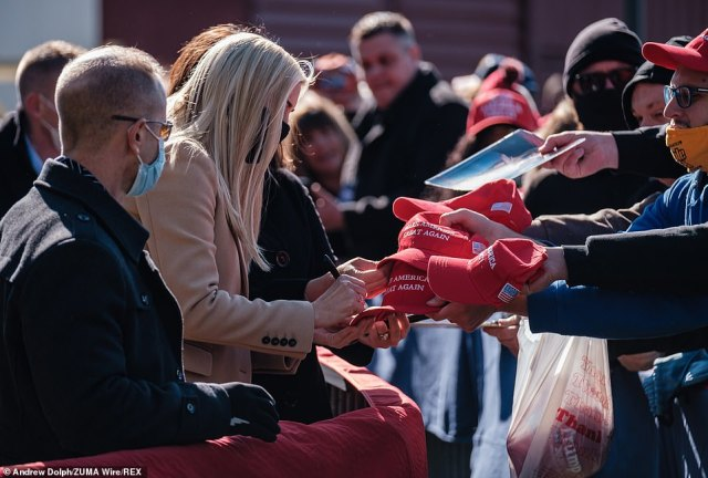 """""""Donald Trump came to Washington for one reason and one reason only: to make America great again,"""" Ivanka said. She is pictured signing MAGA baseball caps in crowd"""