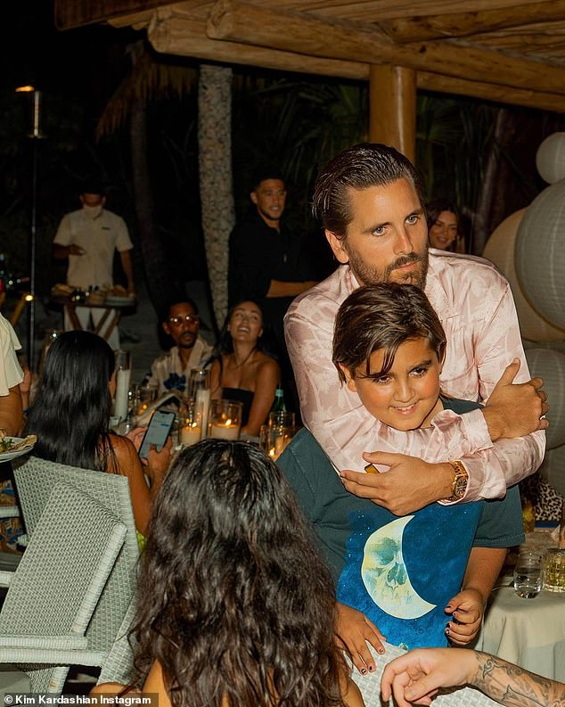 Spotted:None of Kendall's stunning bikini photos featured the pro basketball player, but he was spotted standing near her in a photo Kim shared of Scott Disick hugging his son Mason