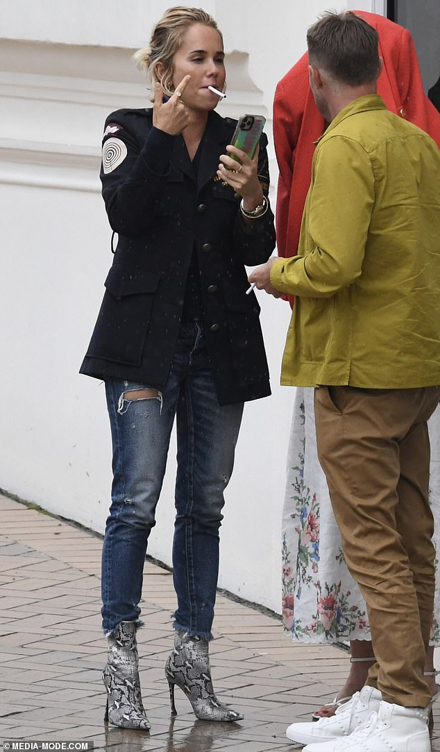 Puffing away: Pip Edwards, 40, took a break from her healthy lifestyle on Sunday as she smoked a cigarette during an outing with her boyfriend Michael Clarke, 39, and friends in Coogee