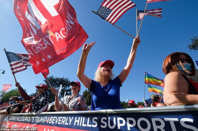 People hold signs and wave US flags during a pro-Trump rally in Beverly Hills, California on Saturday