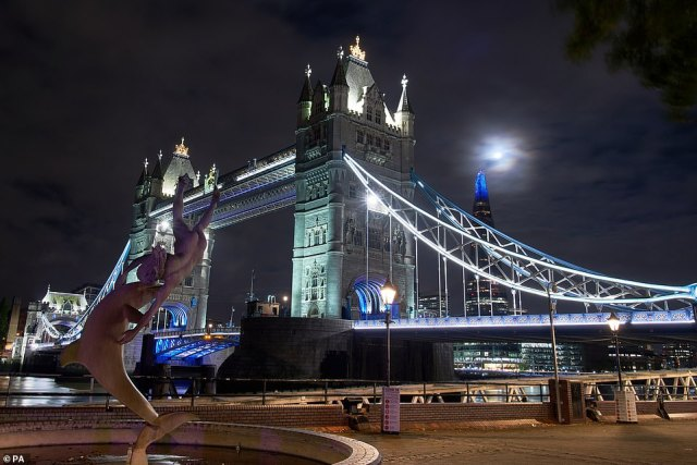 Britons were on Saturday treated to the spectacular sight of the first Halloween Blue Moon in 40 years. Pictured: The moon visible above Tower Bridge in central London