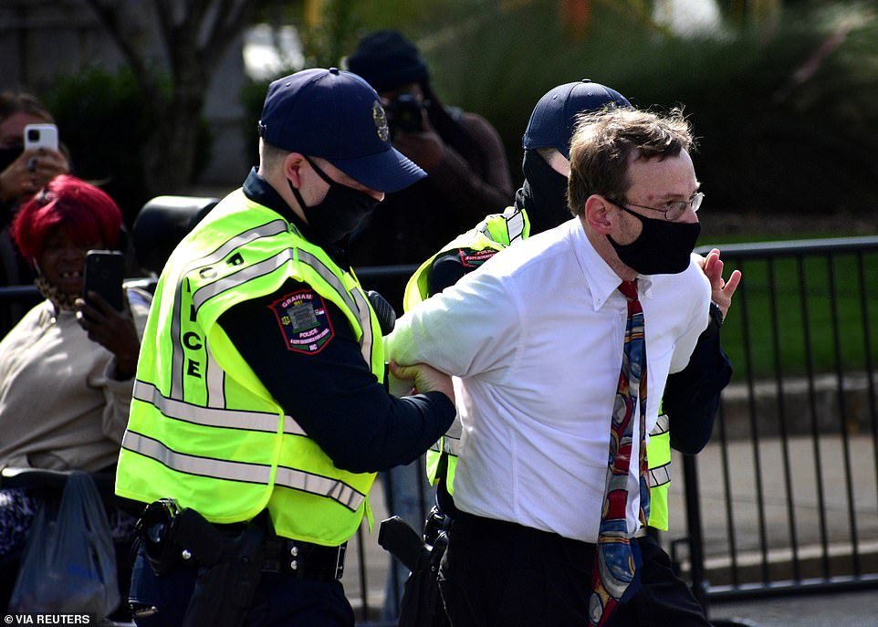 Tomas Murawski, a reporter from The Alamance News is detained by Graham Police officers during the march
