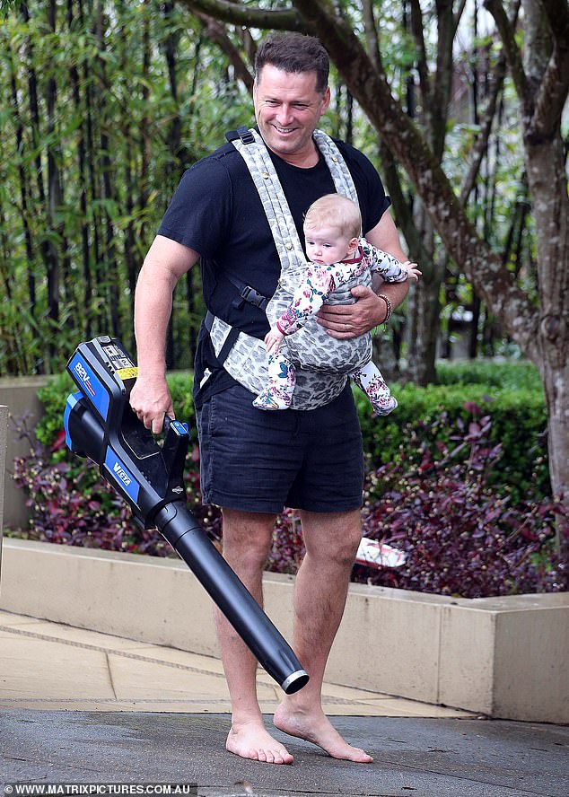 DIY daddy! Today Show's Karl Stefanovic, 46, (pictured) effortlessly juggled daddy duty with yard work on the Sunday, with his six-month-old daughter Harper strapped to his chest