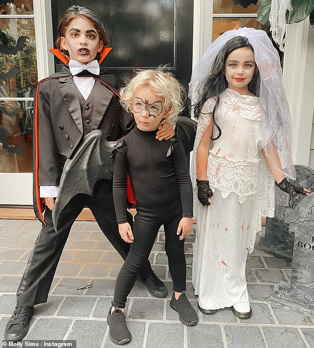 Spitting image: Their son Brooks Alan, eight, and daughter Scarlett May, five, looked adorable in miniature versions of their parents' costumes, as youngest son Grey Douglas, three, made the cutest vampire bat