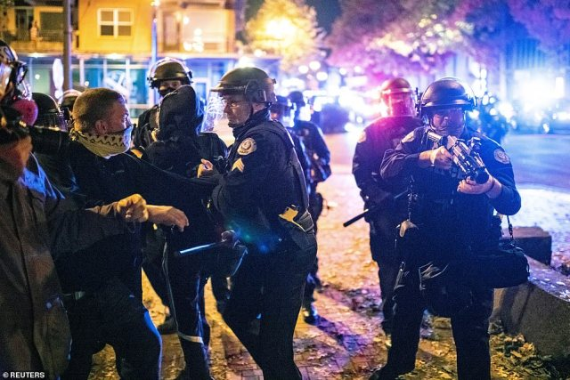 Police detain protesters after a vigil and march marking the shooting death