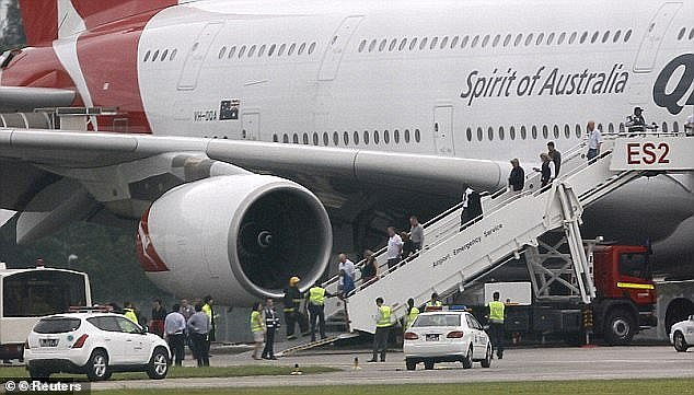 Pictured are passengers alighting the plane at Changi airport after the mid-air emergency