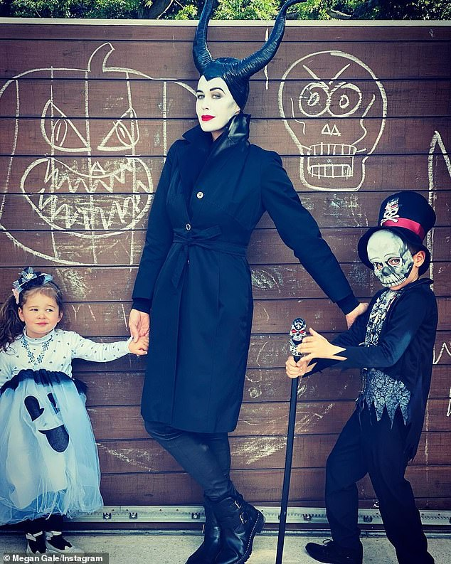 Doting mother: Model Megan Gale, 45, dressed as Disney's Maleficent. She posed with her adorable children, son River, six, and daughter Rosie, two, who went as a 'little ghost and voodoo man'