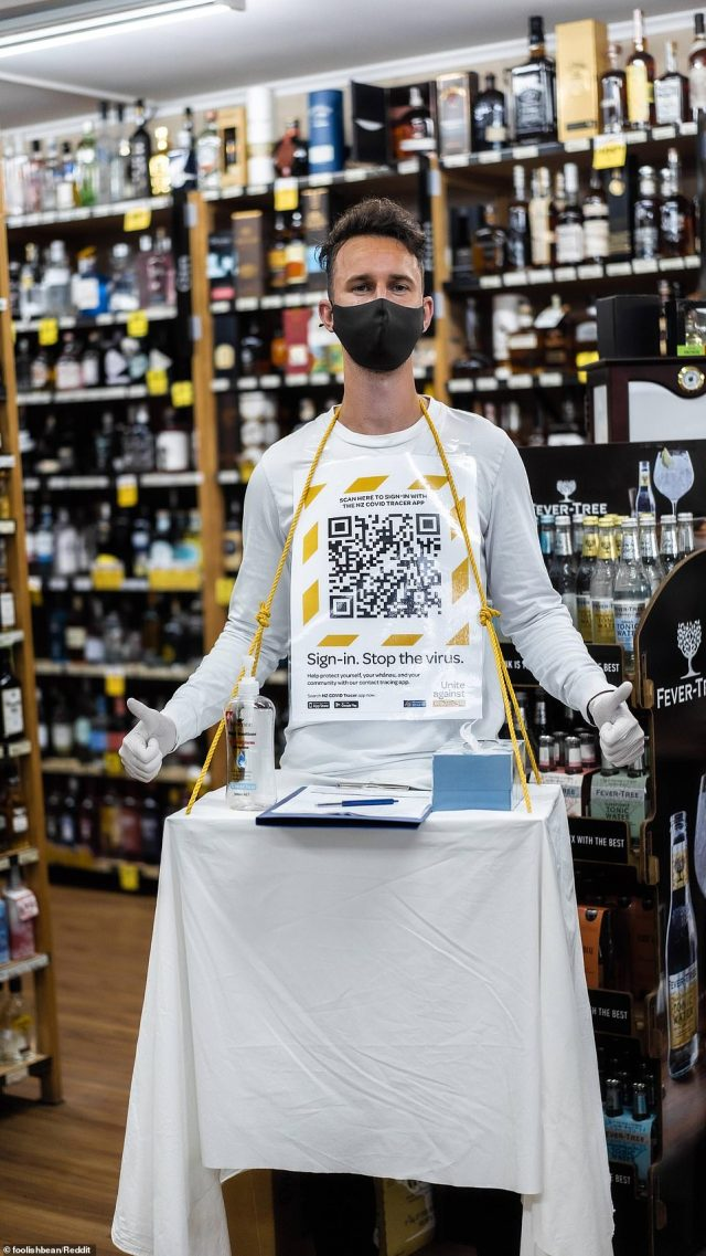 One man dressed as a COVID-19 venue check-in station, complete with hand sanitiser, a barcode, a sign-in sheet and tissues