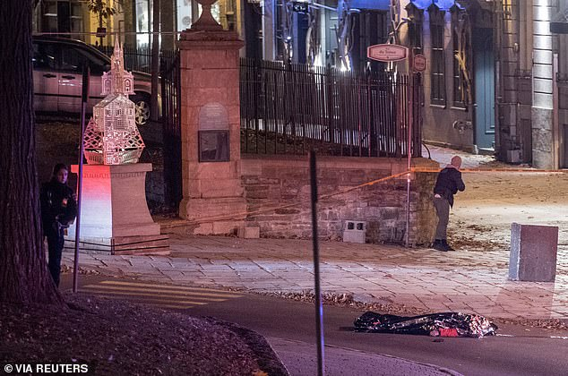 Police officers search near a covered body close to the scene of the stabbing