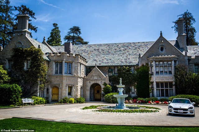 The home is located just two doors down from the Playboy Mansion in Holmby Hills (above)