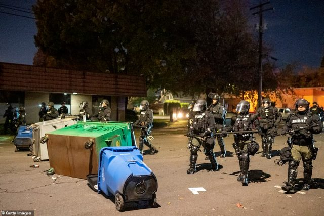 Protester knocked over garbage bins in an effort to create barriers and slow police response