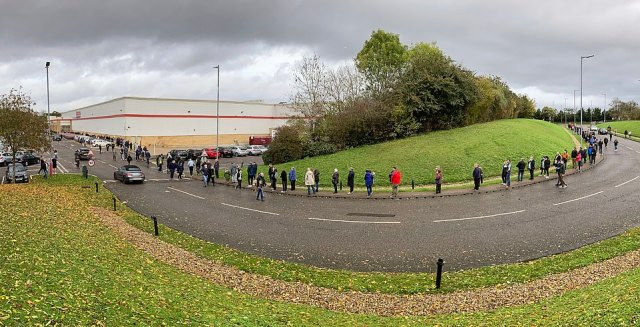 A queue of shoppers snaked along a road outside a Costco in Watford on Sunday