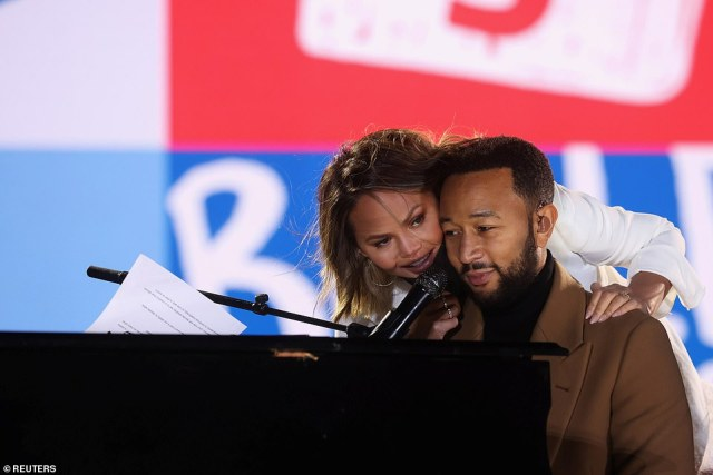Chrissy Teigen (left) leans over her husband John Legend (right) Monday night in Philadelphia as he performs at a rally headlined by Democratic vice presidential nominee Kamala Harris