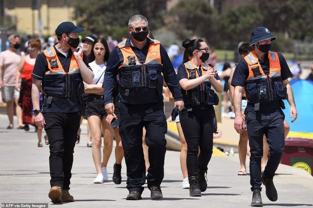 Local officers patrol while people enjoy the warm weather on Melbourne's St Kilda Beach
