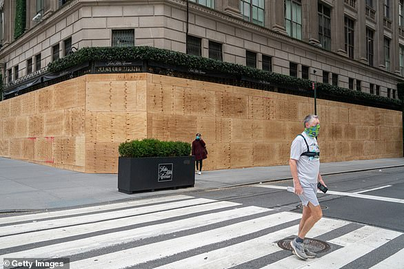 Locals walk by a boarded up Saks Fifth Avenue in New York City on Sunday. The stores were boarded up in anticipation of election-related unrest