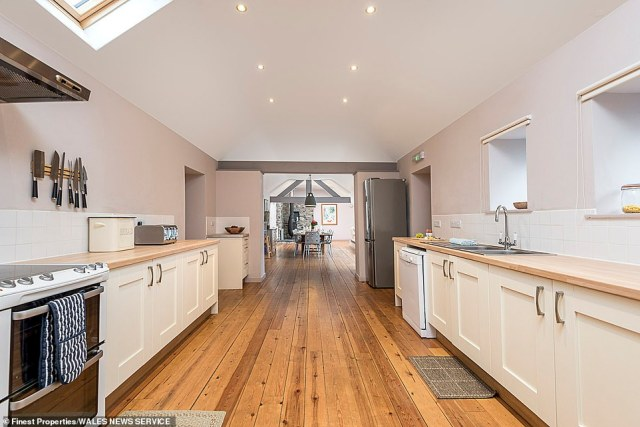 The kitchen inside the former cow shed, which has been renovated into a self-catering luxury cottage, decked with wooden flooring and connecting to the dining area.Paddocks on the site also have the potential to expand the holiday business