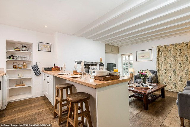 The kitchen area in the Stable Cottage, one of the former outbuildings which have been renovated into a luxury self-catering cottage, featuring wooden flooring, stools and surfaces, alongside shelves for storage space and a door leading outside