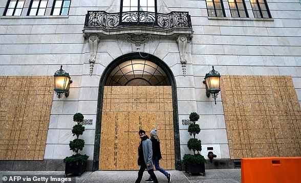 A Bergdorf Goodman store on Fifth Avenue is boarded up on Sunday as a couple walks by the location