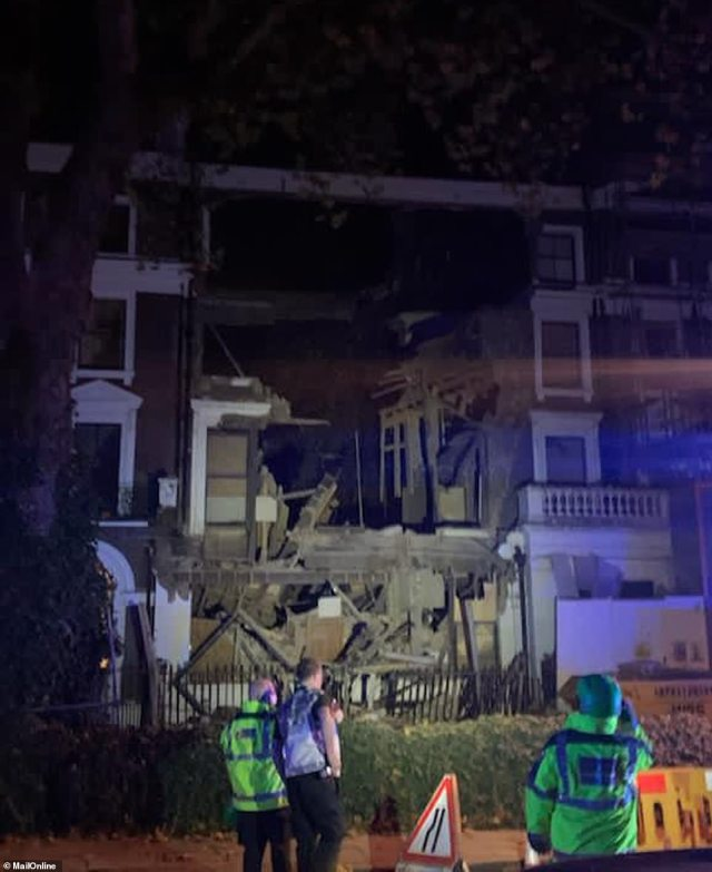 Emergency crews lit up the property after it fell into itself in the early hours of today with rubble and wreckage strewn aside