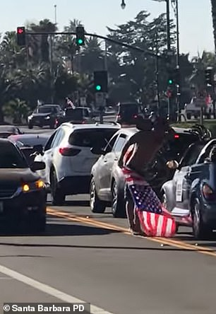 The video shows the male suspect dressed in just beach shorts in the middle of the road holding an American flag and flipping the bird at cars driving past